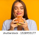 Small photo of Cheat Meal. Happy Girl Eating Burger Standing Over Yellow Background. Studio Shot