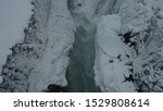 Small photo of View from drone of frozen waterfall falling into Gullfoss canyon during winter afternoon in Iceland. Dark water drops on stones, ice and white snow seethe and foam