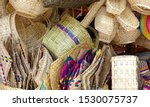 Handmade crafts - woven straw bags and baskets, placemats, fans and others in the craft market of Cuenca, Ecuador