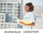 Small photo of Cheerful altruist woman holding notebook outdoors on urban background
