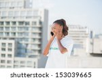 Small photo of Cheerful altruist woman on the phone covering her ear outdoors on urban background