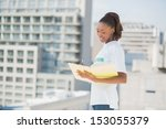 Small photo of Smiling altruist woman holding notebook outdoors on urban background