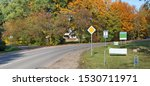 At the bend of the rural road, road signs and advertising banners are installed. Sunny October autumn day panoramic lamdscape