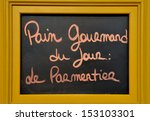 """Advertisement board at a French bakery.The text tells the people in French that the bread of the day is called :""""le Parmentier"""". - stock photo"""