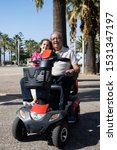 Small photo of Grandfather and granddaughter driving a motorized chair