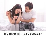 Couple dreaming to be parents. Upset man comforting his depressed wife with negative pregnancy test, free space