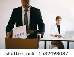 Small photo of Front view with the male employee standing holding office supplies in the paper box going to submit a resignation letter while a female employee is working behind.