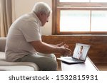 Elderly 70s man seated on sofa make distant video call, senior patient look at laptop screen communicating with doctor therapist online, older generation and modern tech application easy usage concept - stock photo