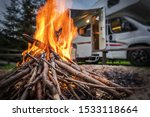 RV Park Campfire in Front of Motorhome Pitch. Summer Camping with Motorhome. - stock photo