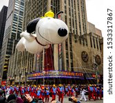 Small photo of Snoopy balloon floats in the air during the annual Macy's Thanksgiving Day parade along Avenue of Americas with the Radio Music Hall in the background. Manhattan, New York, USA - November 27, 2014.