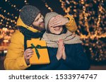 Small photo of Guess who? Photo of two people couple guy closing eyes lady waiting surprise holding her x-mas giftbox wear jackets caps scarfs newyear spirits atmosphere park outside