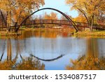 Beautiful fall landscape with stylish bridge in the city park. Scenic view with colored trees and bridge in sunlight reflected in the lake Mendota bay water. Tenney Park, Madison, Wisconsin, USA.