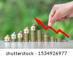 Small photo of House on a pile of coins.Stack of coins arranged in ascending order.The investor's hand catches the red arrow.Business investment ideas.Concept of real estate investment.Business growth.