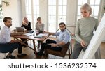 Small photo of Focused multiethnic business people listen old middle aged businesswoman trainer coach teacher explain project strategy pointing on whiteboard give conference presentation training staff at workshop
