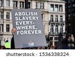 "Small photo of London, UK. October 20 2019. A Walk for Freedom protestor with a sign that reads ""Abolish Slavery Everywhere Forever"" Walk For Freedom is a global fundraising and awareness event."