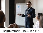 Small photo of Confident male business trainer coach leader give flip chart presentation at office training, businessman conference speaker wear suit teach executive group explain strategy at corporate workshop