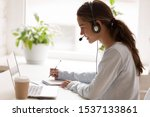 Small photo of Side view concentrated millennial mixed race woman wearing headset with microphone, looking at laptop screen, listening educational webinar, taking notes, getting remote online education at home.