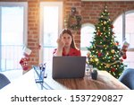 Small photo of Beautiful woman sitting at the table working with laptop at home around christmas tree Showing middle finger, impolite and rude