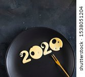 Small photo of Figures 2020 made of cheese with holes on a black plate with small gold fork on chalk board background, top view, Square, copy space. Christmas and New year concept of proper nutrition, food, menu.