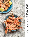 Scampi served with lemon on the beach - stock photo