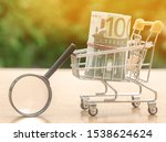 Small photo of Euro banknotes in a shopping trolley and magnifying glass. The concept of finding sources of investment and sponsors. Find a money. Charitable funds. Startups and crowdfunding. Search for cheap loans
