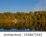 Small photo of Early autumn colour surrounding small cottage with red roof on quiet lake and reflections in northern Ontario near Parry Sound