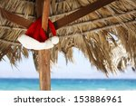 Small photo of Hanging Santa Claus hat on palmy sunshade on beach