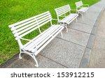 A White Bench In A Green Garden