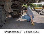 Small photo of 18-Wheeler Pre-trip Tire Inspection - A professional driver is using a tire thumper to check the tires underneath his trailer prior to driving OTR.
