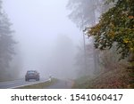 Behringersdorf, Germany - October 24, 2019: A car is driving on a countryside road with a bicycle path along leading through a forest with dense fog. Seen in October in Germany in Franconia / Bavaria. - stock photo