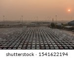 Small photo of Laem Chabang seaport, Thailand - March 17, 2019: Sunrise through fog over parking lot with plus thousand new Dodge sedan cars where Vehicle carriers come and go.
