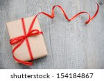 Gift Box With Red Bow On Wood...