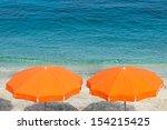 Two Orange Parasol On The Beach.