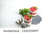 Small photo of Beautiful dessert with fresh berries. Trifle with chocolate and strawberries on a light background copy space.