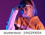 Small photo of Stylish pretty young 20s fashion teen girl model wearing glasses blowing bubble gum looking at camera standing at purple studio background