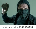 Small photo of fanatic and aggressive anarchist rioter man. furious and scary violent anti-system radical protester in face mask throwing stone looking hostile fighting at riot on isolated background