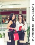 Small photo of Two smiling young women are looking at camera at the shopping mall. Two adult girls with paper bags are looking at camera at the mall.