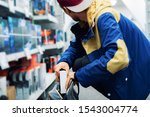 Small photo of close up consumer thief's hands putting the new gadget in the pocket in the store