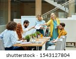 Small photo of Group of young joyful guys in good mood, disscuss work related issues in roomy modern office. Designers meeting concept