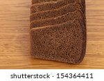 Slices of brown bread on a wooden table. - stock photo