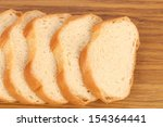 Sliced white loaf of bread on wooden table. - stock photo