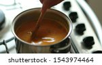 Small photo of Person stirring orange healthy soup