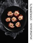 Small photo of Original Halloween snacks. Eyeballs cooked from ham with mozzarella, olives stuffed with red pepper