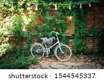 Vintage white bicycle with a basket of flowers on a background of a brick wall in the garden