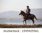 Cowboy Riding Horse In Lake...