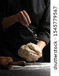 Small photo of Chef cook baker sprinkles flour on a dough for cooking pastries, bread and pizza. Recipes and home cooking. Baking Recipe Book, Vertical Photo