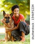Stock photo photo of woman with a german shepherd in a grass field 154691234