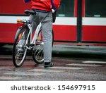 Man in red, in rain, on bike, waiting, in traffic - stock photo