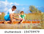 father bandaging injured leg of ... | Shutterstock . vector #154759979