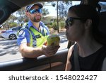 Small photo of PERTH, WA - OCT 27 2019:Australian traffic police officer using breathalyzer on woman driver during field sobriety testing.Traffic accidents are predominantly caused by Impaired driving